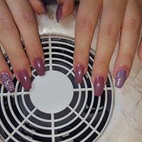le mani di una donna mentre asciuga lo smalto viola davanti un fornetto