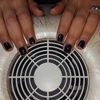 le mani di una donna mentre asciuga lo smalto nero sulle unghie davanti un fornetto