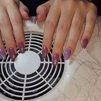 Le mani di una donna mentre asciuga lo smalto davanti a un fornetto