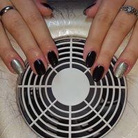 Delle mani di una donna con smalto di color nero chiaro e alcune unghie di color argento