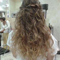 Una donna vista dal dietro con capelli ricci di color castano scuro