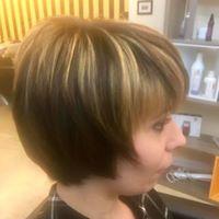 Una donna con capelli biondi tagliati corti con una frangetta
