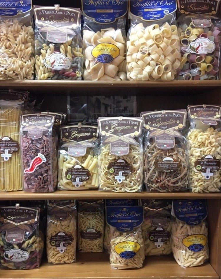 delle confezioni di pasta esposte in uno scaffale di legno