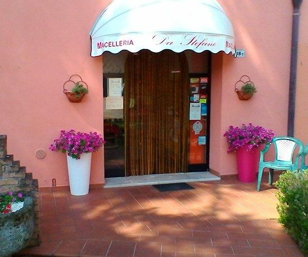 vista dall'esterno dell'entrata alla macelleria con sopra una tenda bianca e sui lati dei vasi con dei fiori viola e una sedia di plastica color turchese