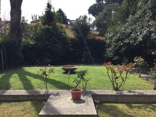 giardino con grandi vasi in terracotta e murretto in cemento