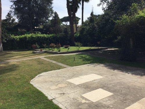 spiazzo asfaltato in mezzo a un giardino collegato a un sentiero