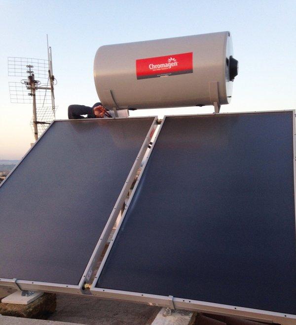 un operaio sta installando due pannelli di color blu su un tetto con sopra una tanica in ferro grigio con scritto Chromagen