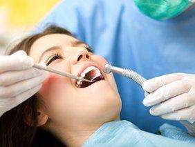 woman getting teeth cleaned - Live Oak Family Dentistry