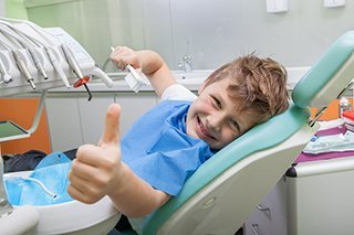 child giving thumbs up in dentist chair - Live Oak Family Dentistry