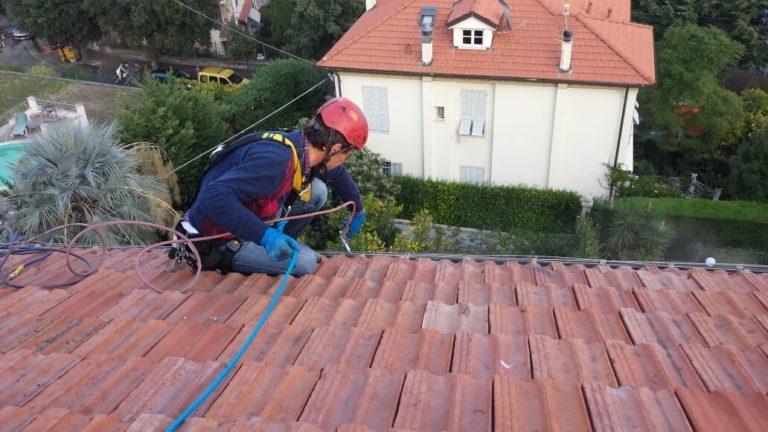 Uomo con imbragatura di sicurezza che esegue lavori di riparazione sul tetto