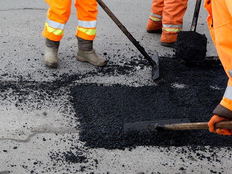 operatori sistemando l'asfalto