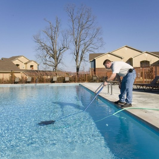 Man cleaning pool with long device