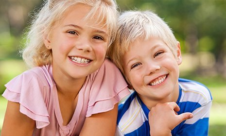 Two kids smiling after seeing a pediatric dentist in La Crosse County, WI