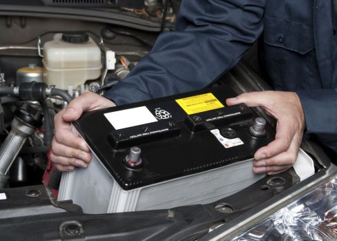 Expert installing battery at MOT testing station in Crofton