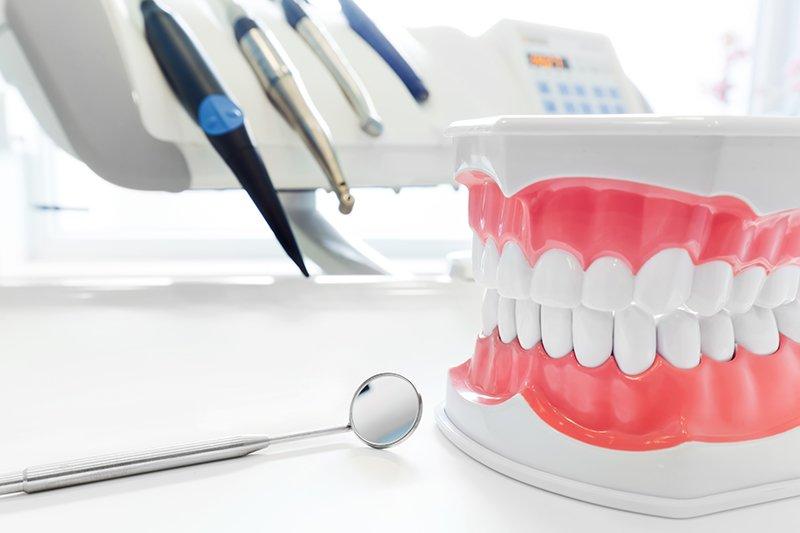Pulire i denti protesi, il modello della mascella dentale, specchio e odontoiatria strumenti in ufficio del dentista.