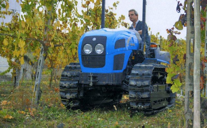 vista frontale di una macchina agricola blu con addetto alla guida
