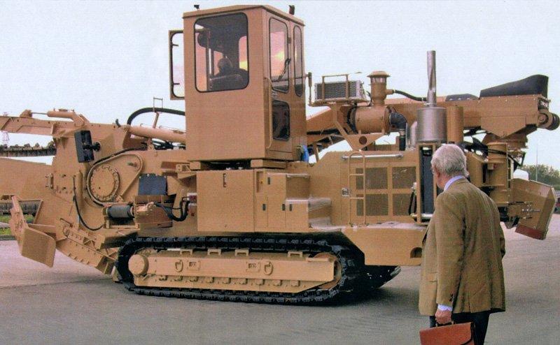 macchina agricola cingolata con un uomo che la guarda e un addetto alla guida