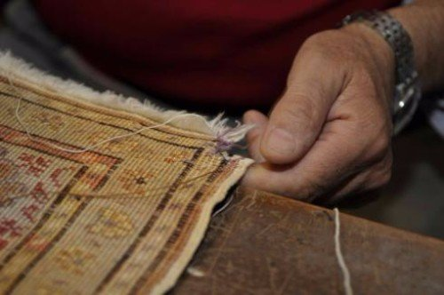 una mano che tiene il bordo di un tappeto