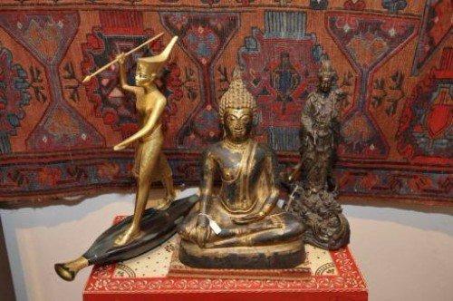 tre statue e dietro un tappeto di diversi colori