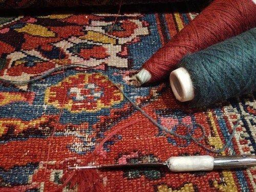 un ago,due rocchetti con del filo e un tappeto