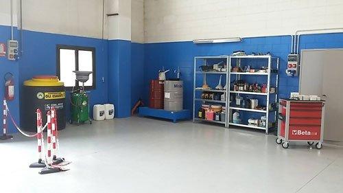 Autofficina con pareti blu e scaffalature con attrezzi