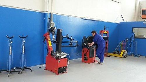 Uomo in tuta blu che lavora ad un macchinario rosso in un'autofficina