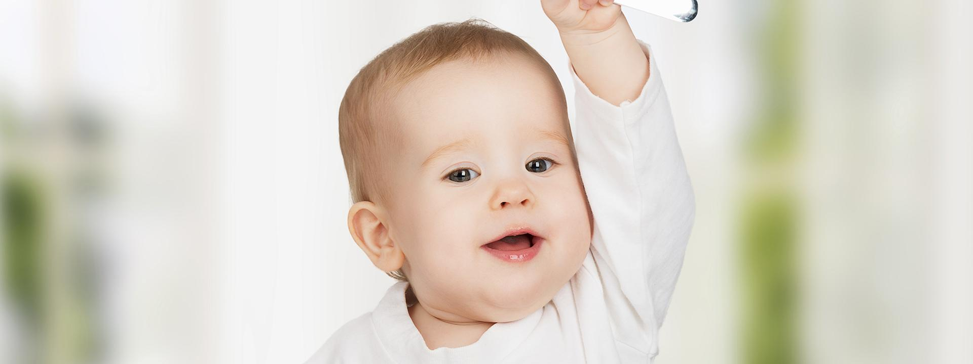 Bambino sorridendo e alzando la mano