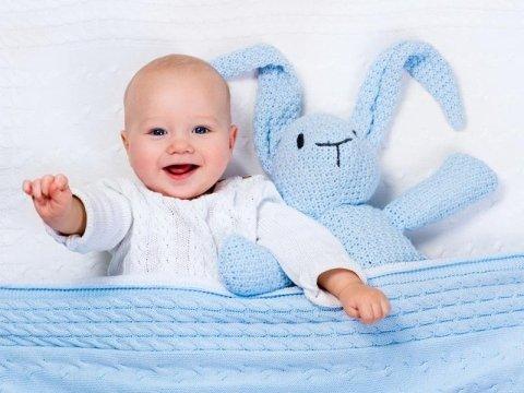 Bambino sorridendo accanto a un grande coniglio blu