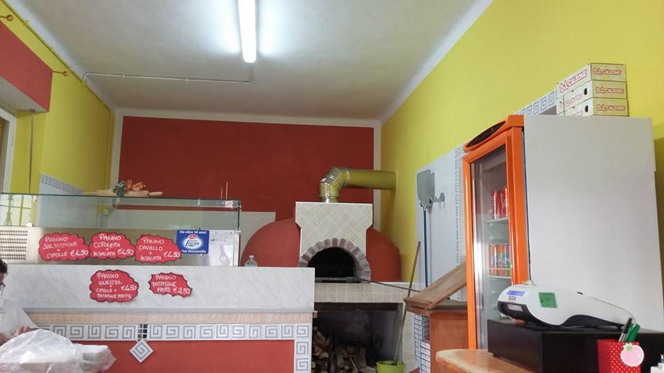 interno della pizzeria con vista del forno