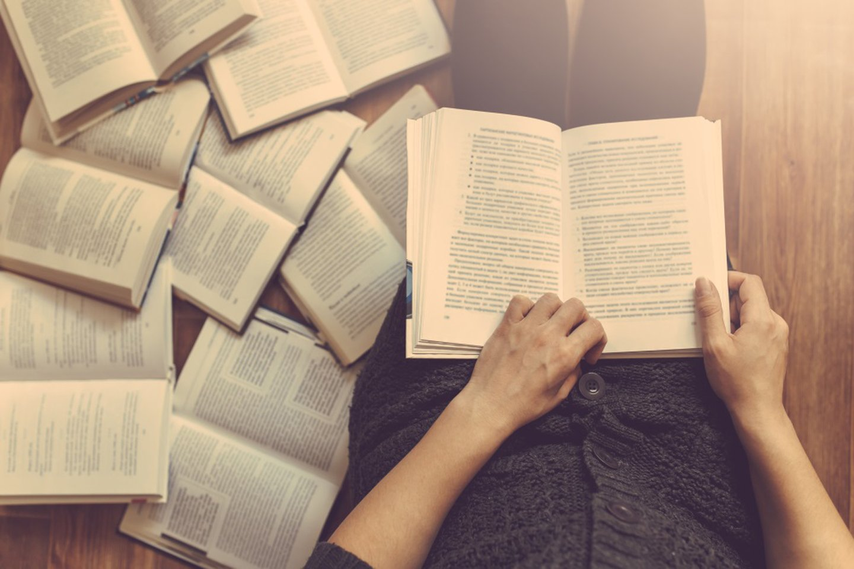 persona in mezzo a dei libri aperti