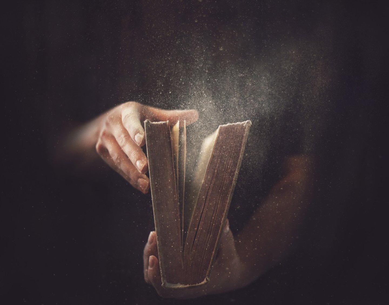 persona che apre un libro con fuoriuscita di polvere