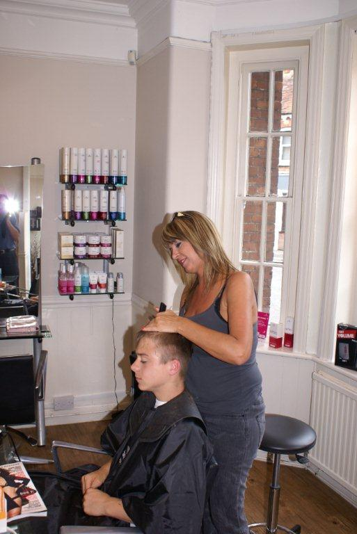 A stylist cutting a young man's hair