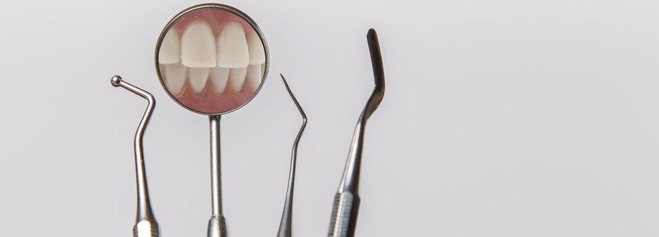 degli strumenti da dentista con riflesso dei denti
