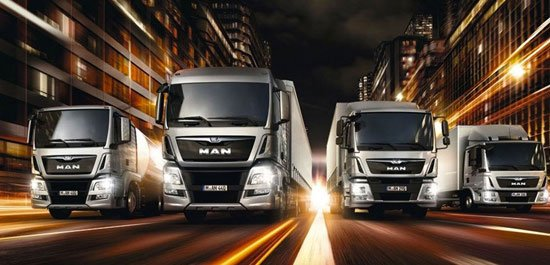 quattro camion della marca Man sulla strada con delle luci accese