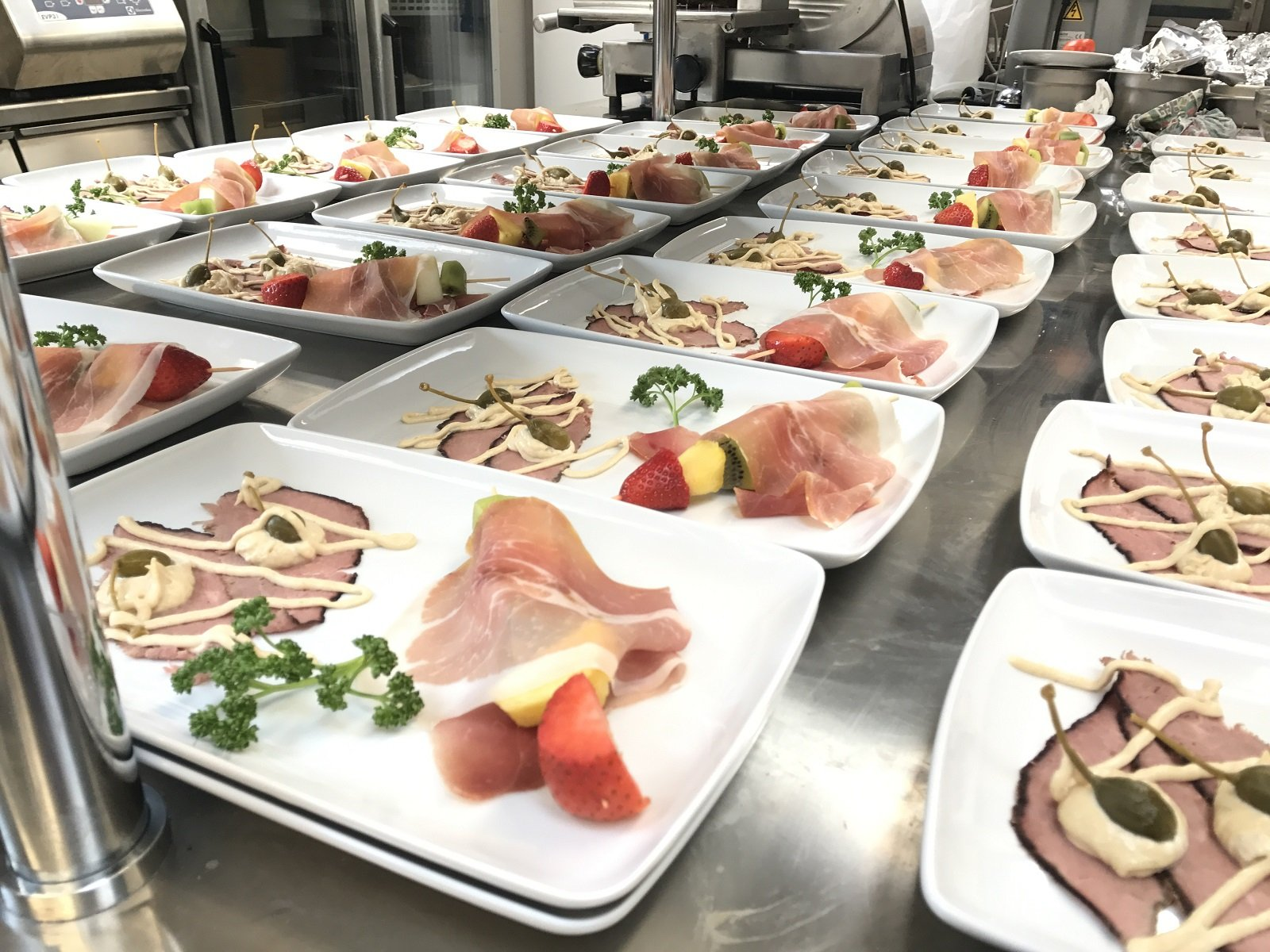 Diverse varietà di fette di carne, formaggio, prosciutto e salame su un banchetto