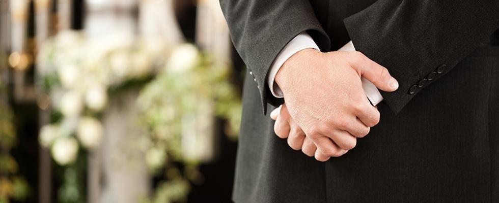 Dettaglio delle mani congiunte di un impresario funebre