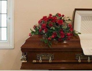 Dettaglio di un feretro don cuscino funebre di fiori rossi