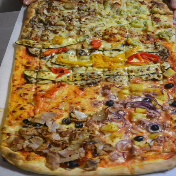 Super pizza con varietà di ingredienti per essere servita al taglio