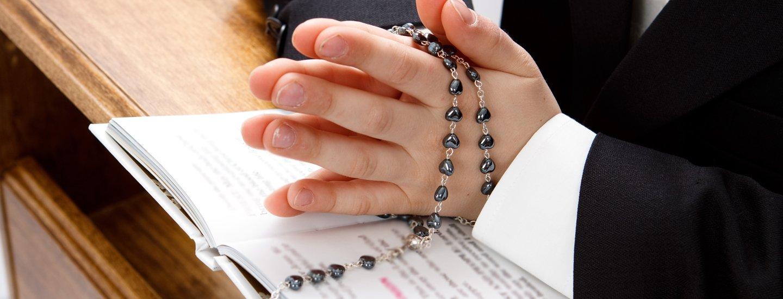 bambino che prega con rosario in mano