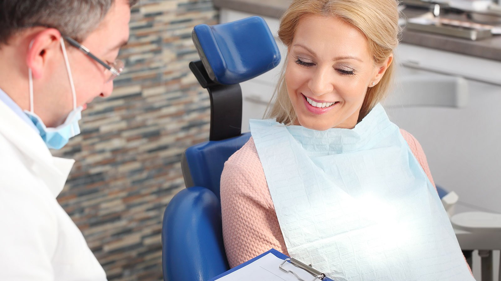 a smiling woman next to a dentist