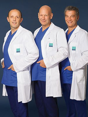 three dentists with blue scrubs and white jackets