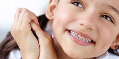 una bambina sorridente con un apparecchio dentale