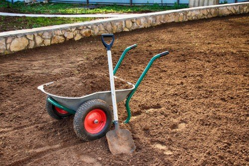 a wheelbarrow and a shovel in the soil