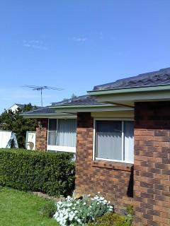 all oz roof plumbing brick house with light green gutter near roof top