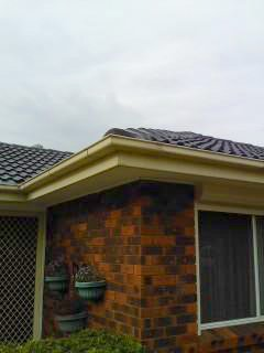 all oz roof plumbing brick house with roof gutter running near along the corner