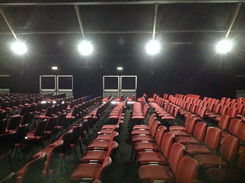 Sedie rosse da cinema con porte antipanico per l'uscita d'emergenza