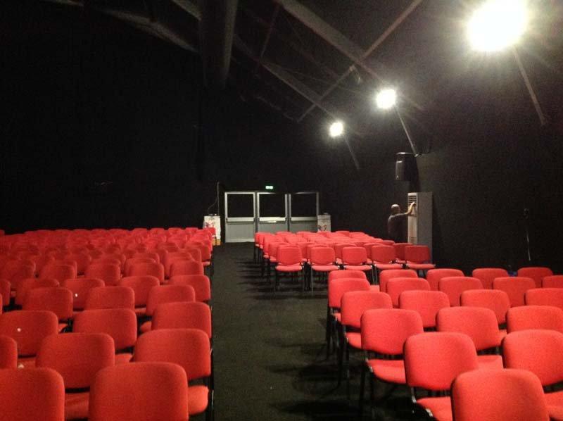 Sedie rosse da cinema in capannone oscurato