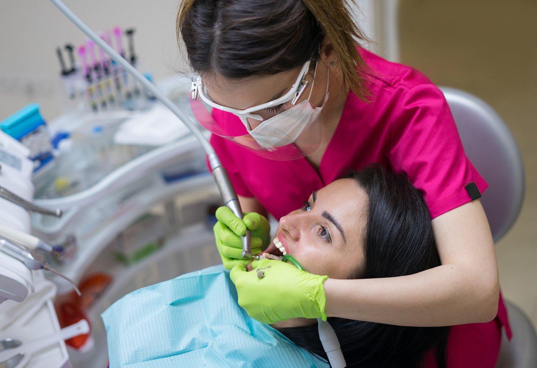 Dentista che esegue la cura di un dente al cliente