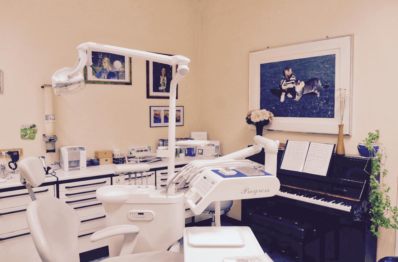 poltrona da dentista nello studio  con quadri e pianoforte