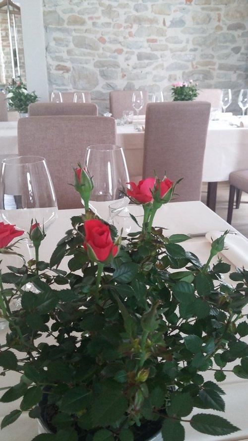 tavoli apparecchiati con bicchieri per il vino e mazzo di rose rosse